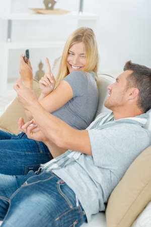 livingroom: Funny couple fighting over the television remote Stock Photo