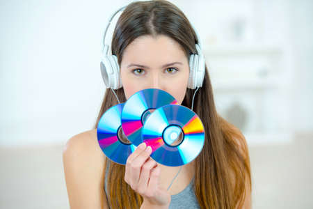compact: Lady with headphones holding three CDs