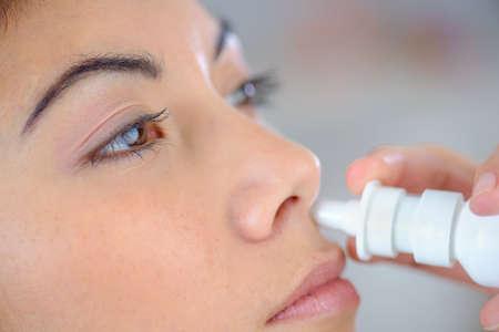 nariz: Mujer que usa un aerosol nasal Foto de archivo