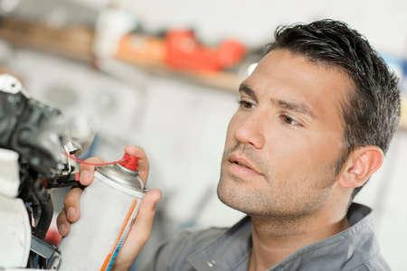 Mécanicien en utilisant la lubrification pulvérisation Banque d'images