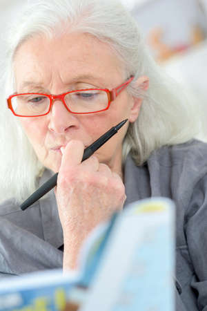 elderly adults: Old last doing a crossword Stock Photo