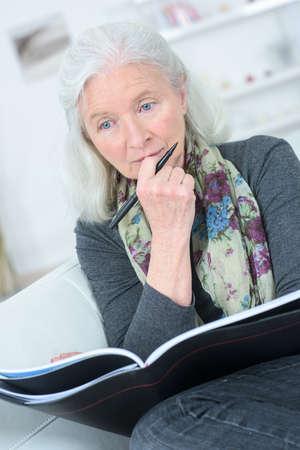 alte dame: Old lady reading on the sofa Lizenzfreie Bilder