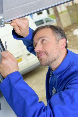 door: Man installing a garage door