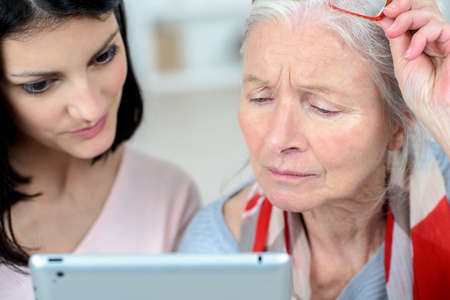 widow: Helping old woman use a tablet computer