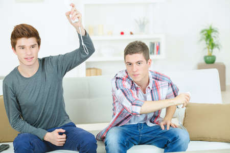 gamer: Two male friends playing video games Stock Photo