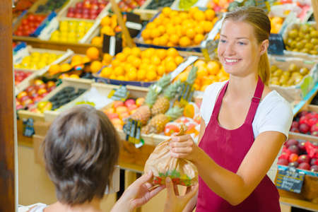 sell: Greengrocer  serving a customer Stock Photo