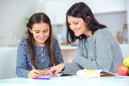 Мама помогает дочери делать домашнее задание Фото со стока