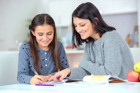 helping children: Mom helping her daughter do her homework