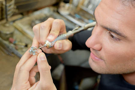 jewel hands: Skilled jeweller repairing a ring Stock Photo
