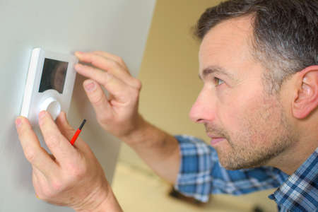energy electrician: Electrician fitting a thermostat system
