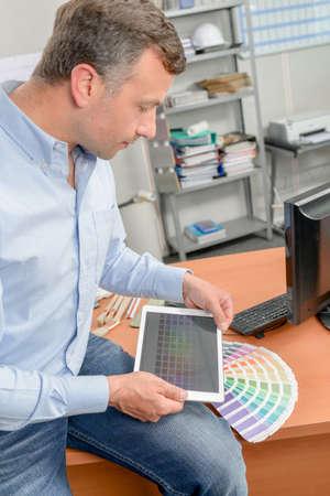 sat: Designer sat on the edge of his desk