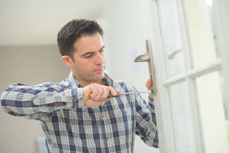 screw key: Handyman fitting a new door