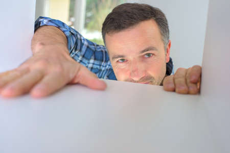 redecorate: Kitchen fitter installing a cupboard Stock Photo