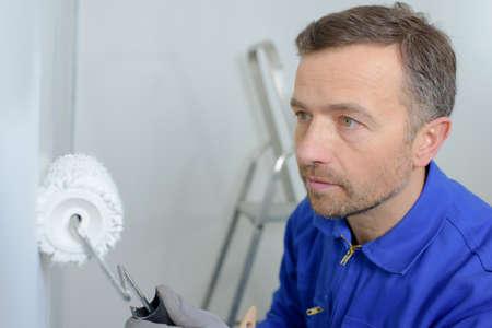 competencias laborales: Hombre que pinta una pared blanca Foto de archivo