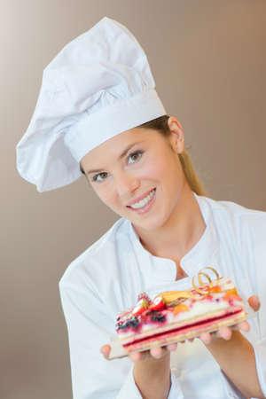siervo: Cocinero de sexo femenino panadería con un pastel de frutas