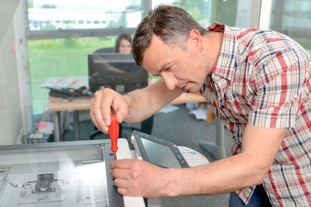 Handyman fixant l'imprimante de bureau Banque d'images