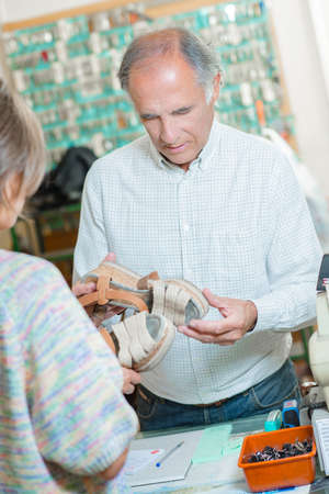 cobbler: Cobbler looking at a womens damaged shoes Stock Photo