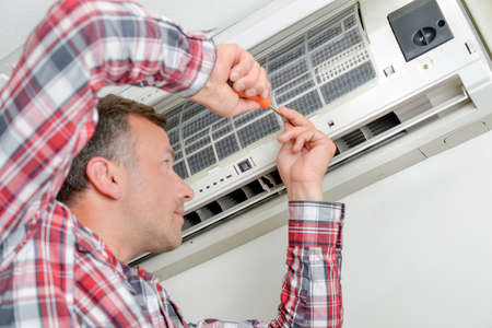 aire puro: Hombre que trabaja en la unidad de aire acondicionado