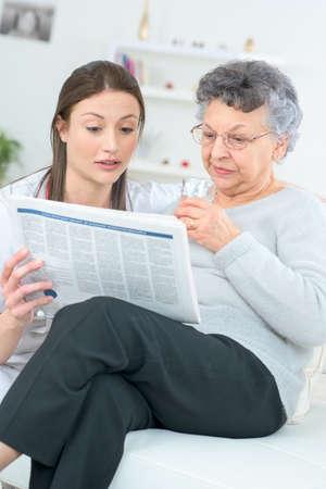oude krant: Het lezen van een krant met een oude dame