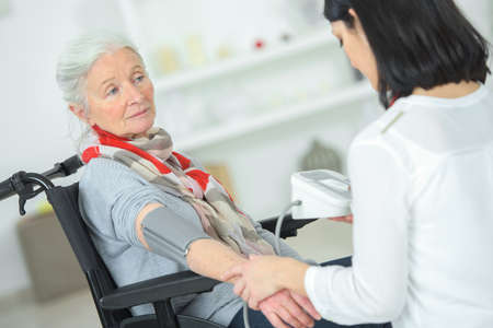 ladys: Checking an old ladys blood pressure Stock Photo