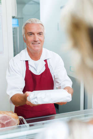 congenial: Butcher passing a package to a customer