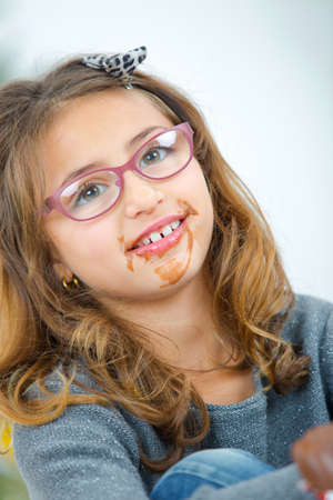giggling: Little girl with chocolate around her mouth Stock Photo