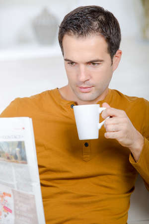 whilst: Man drinking coffee whilst reading the newspaper Stock Photo