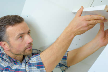 maintenance fitter: Worker fitting a kitchen Stock Photo