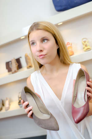 Woman cant decide which shoes to buy Stock Photo