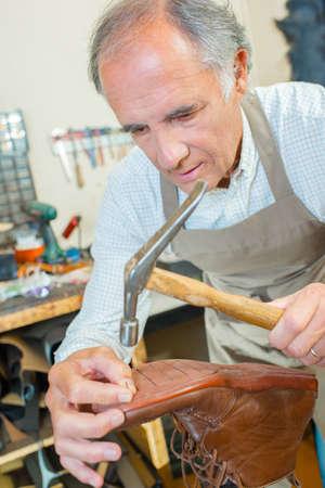 cobbler: Cobbler using a hammer Stock Photo