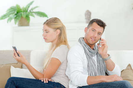 bad manners: Couple both using their phones on the sofa