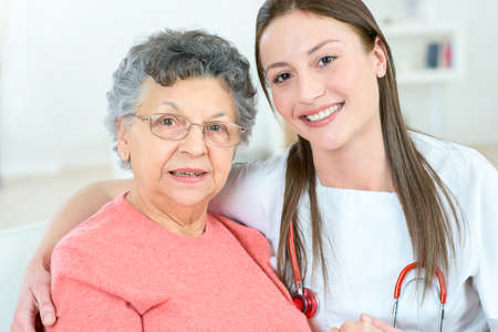 elderly woman: Doctor sat with an old patient Stock Photo