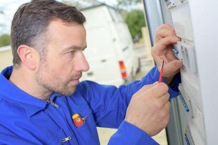 Man inspecter un fusebox endommagé Banque d'images