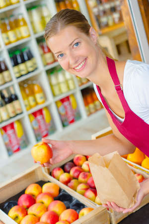 produce sections: Supermarket worker in the fruit section Stock Photo