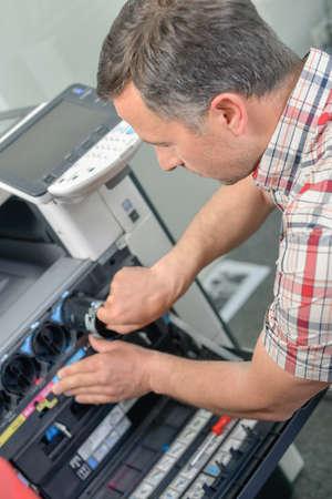computer printer: Man repairing a printer