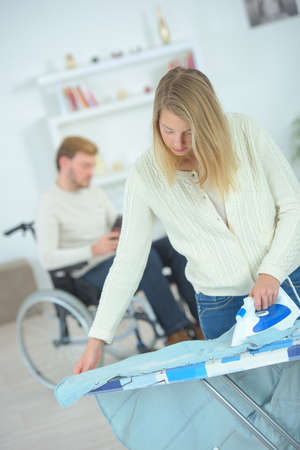 domestic: Woman ironing for her disabled boyfriend