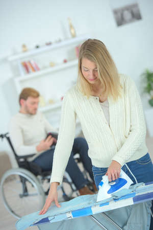 woman ironing: Woman ironing for her disabled boyfriend