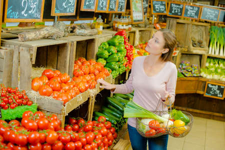 produce sections: Woman browsing the organic section of a supermarket