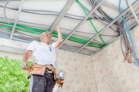 garage: Electrician wiring a garage ceiling