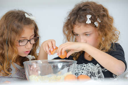 breaking: School girls breaking eggs into a bowl
