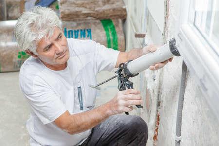caulking: Handyman caulking a window frame