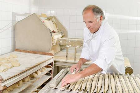 negocios comida: Panadero prepara baguettes Foto de archivo