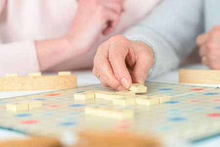 board: Elderly woman playing a board game Stock Photo