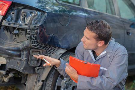assessing: Mechanic holding clipboard assessing car