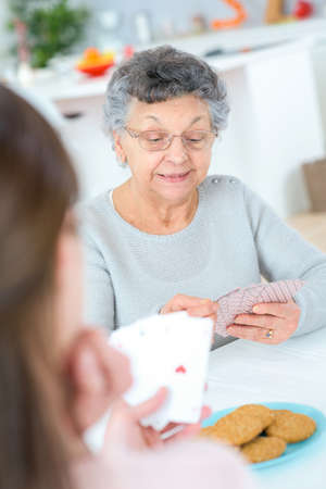 withdrawn: Playing cards with her grandma Stock Photo