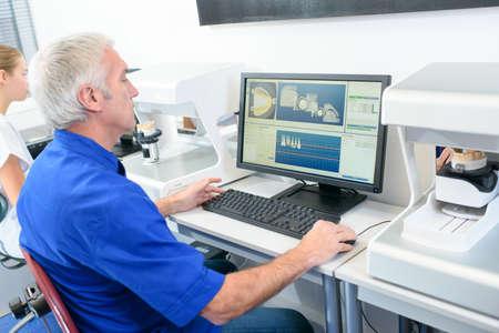 clinical: Senior dentist sat at his desk