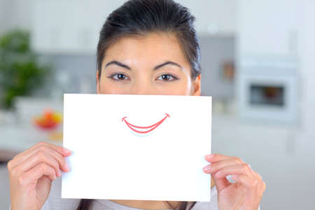 fake smile: Woman holding sheet of paper over her mouth