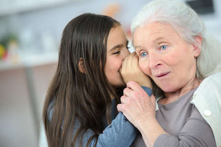 secret: Little girl and grandma whispering secrets Stock Photo