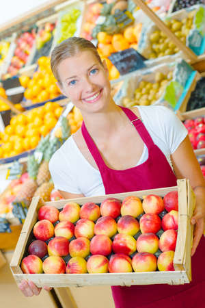 shop assistant: Shop assistant holding tray of nectarines Stock Photo