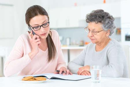 haushaltshilfe: Helfende ältere Dame mit ihren Finanzen Lizenzfreie Bilder